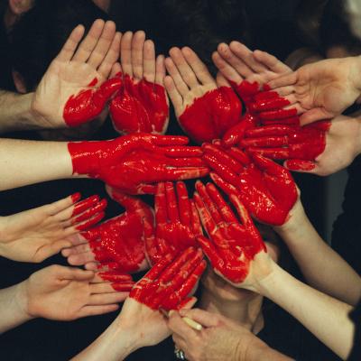 Mehrere rot bemalte Hände formen ein Herz